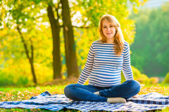 Pregnant girl in jeans and a striped sweater Stock Photo