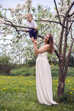 Pregnant girl with long hair wearing a white dress standing  his son on the tree Royalty Free Stock Photography
