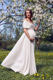 Pregnant girl with long hair wearing a white dress standing Royalty Free Stock Photos
