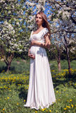 Pregnant girl with long hair wearing a white dress standing. Pregnant girl with long hair wearing a long white dress standing in the street near the Apple trees stock image
