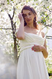 Pregnant girl with long hair wearing a white dress standing Stock Images