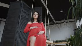 A pregnant girl in a long red dress sits on the swing and gently strokes her belly and looks at him. Conception of. Pregnancy. Happy time slow motion stock video