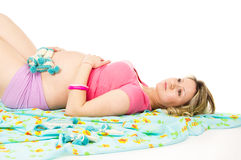 Pregnant girl lying with booties on fabric Stock Photography