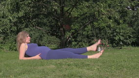 Pregnant girl make exercise leg lie on grass. Prenatal sport stock video footage