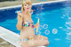 Pregnant girl is making soap bubbles near swimming. Beautiful pregnant blonde woman is making soap bubbles near swimming pool with blue water, vacations Royalty Free Stock Images