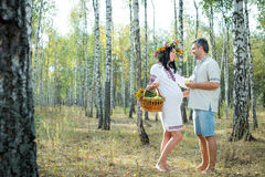 Pregnant girl and man in a birch grove. Royalty Free Stock Images