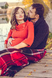 Pregnant girl and man are wrapped in warm blanket Stock Photos