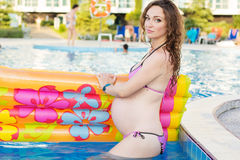 Pregnant girl with mattress near swimming pool Royalty Free Stock Photography