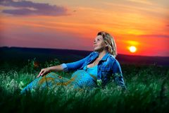 Pregnant girl on nature sky. Red sunset Stock Photography