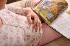 Pregnant girl. In pajamas with  hand on her belly Stock Photography