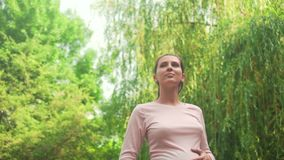 Pregnant girl in the park on background of green willow. Calm girl is standing in the park, holding hands on her tummy. stock footage