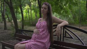 Pregnant girl in the park on a background of trees. A girl in a striped dress sits on a bench and strokes tummy. stock video