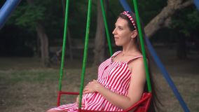 Pregnant girl in the park swinging on a swing. Happy girl with long dark hair in a striped white-red dress on a swing. stock video footage