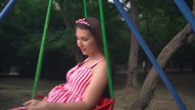 Pregnant girl in the park swinging on a swing. Happy girl with long dark hair in a striped white-red dress on a swing. stock footage