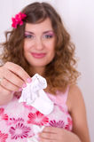 Pregnant girl in pink dress holding baby socks 1. Beautiful pregnant girl with wavy hair wearing pink dress holding baby socks Royalty Free Stock Image