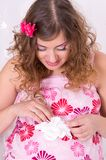 Pregnant girl in pink dress holding baby socks Stock Image