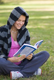 Pregnant Girl reading a book. Reading woman sitting in the grass royalty free stock photo