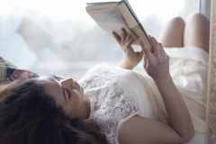 Pregnant girl reading Royalty Free Stock Images