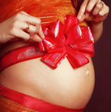 Pregnant girl with a red bow on her stomach Stock Photo