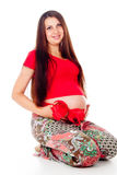 Pregnant girl with a red bow on her stomach Royalty Free Stock Photos