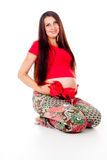 Pregnant girl with a red bow on her stomach Stock Photos