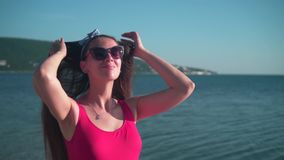 A pregnant girl in a red one-piece swimsuit and glasses is standing on the beach, smiling and touching her hair. stock footage