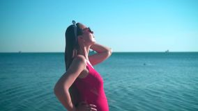 A pregnant girl in a red one-piece swimsuit and glasses is standing on the beach, smiling and touching her hair. stock video footage