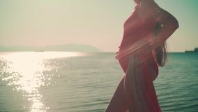 A pregnant girl in a red one-piece swimsuit is standing on the shores of the sea and stroking her tummy. Tummy close up. A pregnant girl in a red one-piece stock video