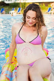 Pregnant girl relaxing near swimming pool Stock Photography
