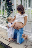 Pregnant girl sits with her son on the street who looks down. On mom`s stomach and touches it Royalty Free Stock Image