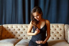 Pregnant girl sitting on the couch in a beautiful dress royalty free stock image