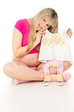 Pregnant girl sitting and holding a baby dress Royalty Free Stock Photos