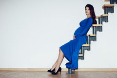 Pregnant girl sitting on a ladder. Beautiful pregnant girl, brunette, big breasts, hands on belly, blue dress, sitting on a ladder against a white wall in the royalty free stock images
