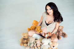 Pregnant girl sitting on the warm floor with teddy bears. Stock Photo