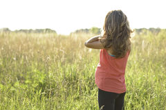Pregnant girl standing in field straightens hair, a bright sunny day woman waiting for child. Royalty Free Stock Photo