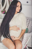 Pregnant girl in studio is wearing white sweater Stock Photography