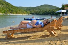 Pregnant Girl Sunbathing By The Beach Stock Photo