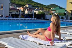 Pregnant girl sunbathing by the pool. Pregnant woman sunbathing on a lounger Royalty Free Stock Images