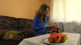 Pregnant girl take out stones from ripe watermelon fruit and eat stock video footage
