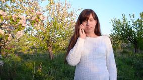 Pregnant girl talking on phone in blossomed spring Park, girl with phone walking in flowered garden in the spring. Pregnant girl talking on phone in blossomed stock footage