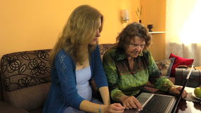 Pregnant girl teach senior grandma how to use laptop computer stock video