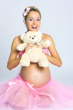 Pregnant girl with teddy bear royalty free stock images
