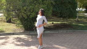 Pregnant girl is walking in city park at sunset. A modern pregnant girl in a gray dress and sneakers is walking in the spring in the park, she is basking in the stock video
