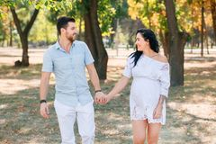 Pregnant girl walks in the park with her husband, hugging and kissing, enjoying the beautiful weather royalty free stock image