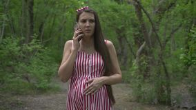 A pregnant girl walks through the park. A girl in a striped white-red dress speaks by telephone and strokes her tummy. stock video footage