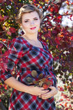 Pregnant girl is wearing checkered dress in park Royalty Free Stock Images