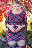 Pregnant girl is wearing checkered dress in park Stock Photos