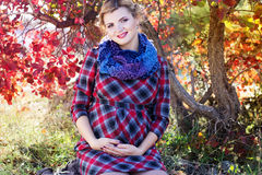 Pregnant girl is wearing checkered dress in park Stock Photo
