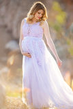 Pregnant girl wearing dress in mountains. Pregnant pretty girl is wearing purple dress on the cliff in mountains over sunset lights royalty free stock photography