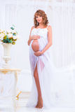 Pregnant girl in a white dress with orchids as a goddess Stock Image